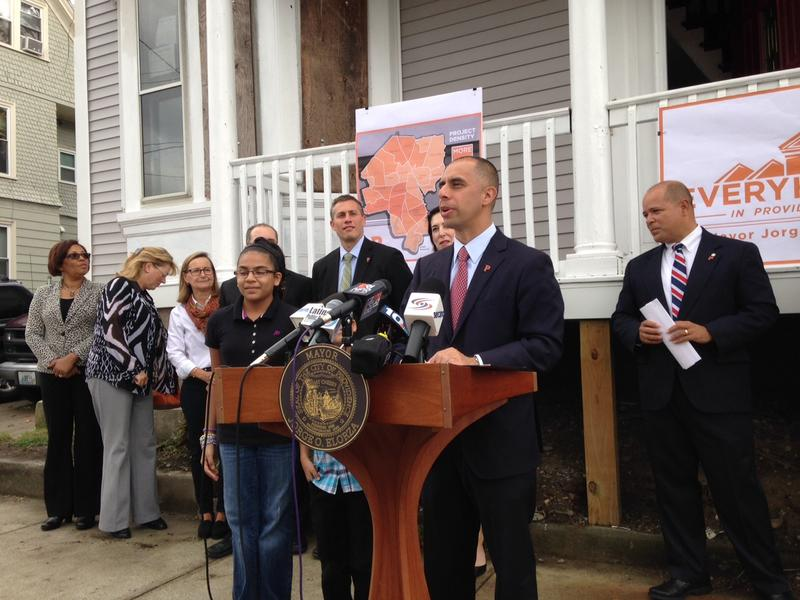 Providence Mayor Jorge Elorza standing in front of two abandoned properties being rehabbed as part of the 'EveryHome' initiative.