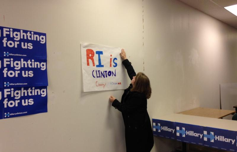 Ann Gooding hangs a poster reading 'RI is Clinton Country' at the Hillary Clinton headquarters in Providence.