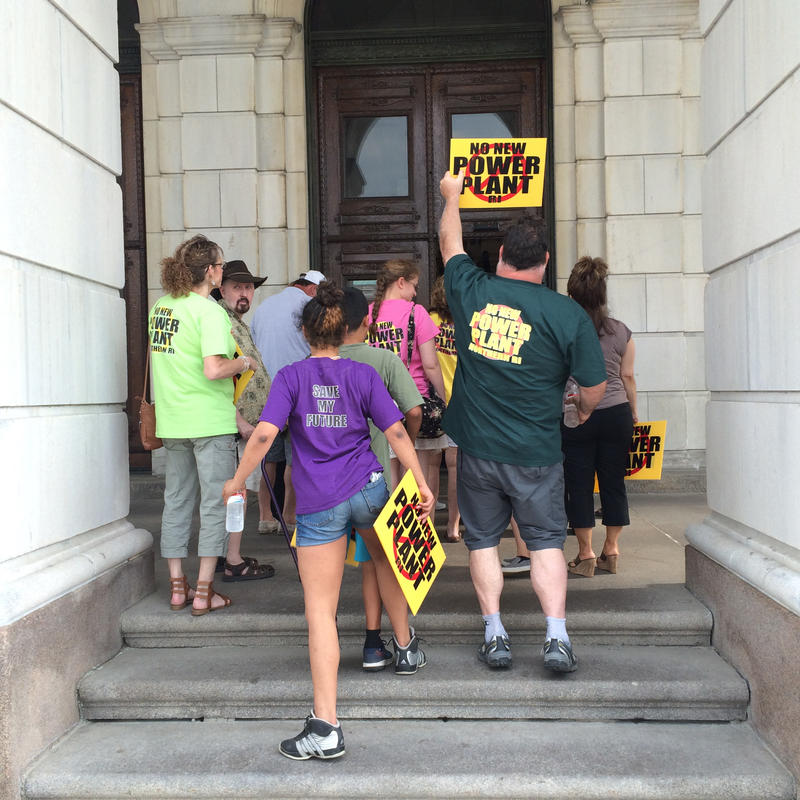 Burrillville residents carpooled to the Statehouse on a school bus to attend a rally in opposition to a proposed power plant in Burrillville and a house committee hearing on a bill related to the project.