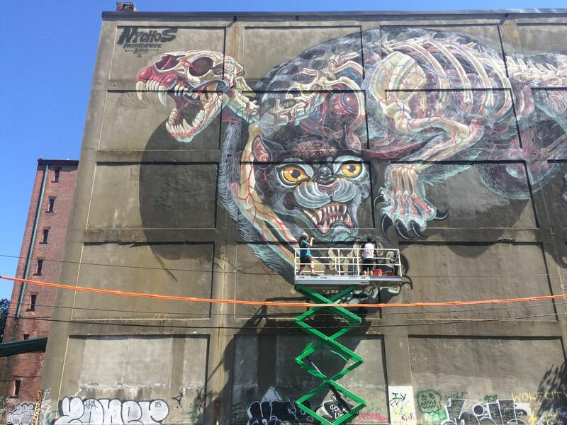 The artist NYCHOS at work on his mural BATTLECAT in Providence.