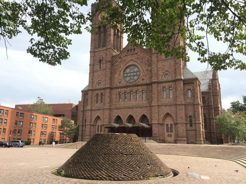 A brick fountain sits in the center of Cathedral Square. A number of bricks are missing or brocken, and weeds grow where water once flowed.