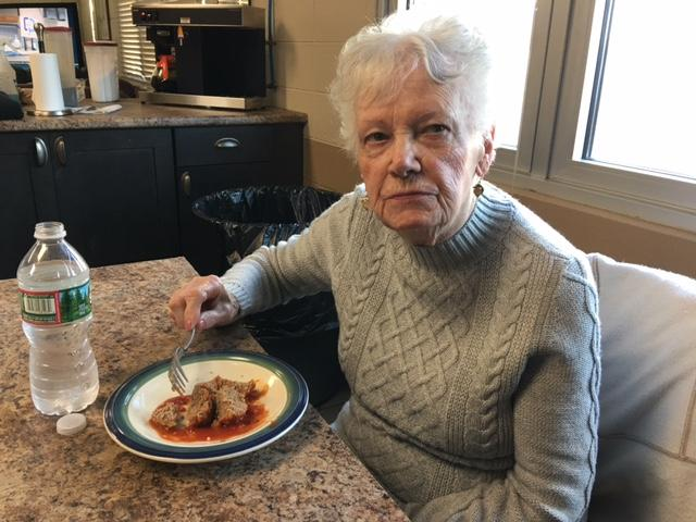Audrey Gesualdi, 92, Johnston resident, and maker of meatballs, tastes the firefighters' creation.