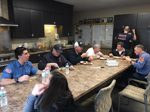 The firefighters sit down to a meatball feast.