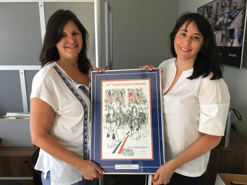 Gail Parella (left) and her sister, Lisa Sienkiewicz, hold a commemorative print of the 232nd Fourth of July celebration in Bristol. They will make history this year as the first ever pair of sisters to lead the parade as co-chief marshals.