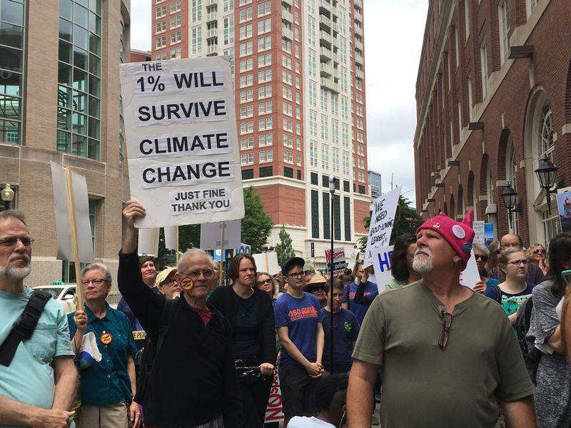 A protester holds a sign at a rally Saturday outside of the National Governors Association's meeting in Providence. Protesters demanded more aggressive state policies addressing climate change.