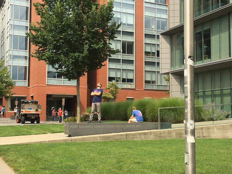 An eclipse viewer stopped outside the Granoff Center at Brown University