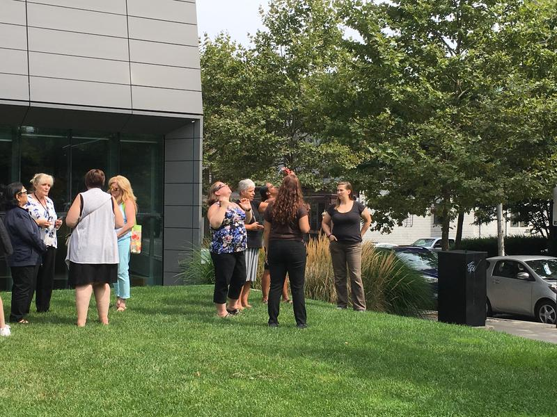 Co-workers and passers-by stopped to watch as the eclipse reached its fullest point.