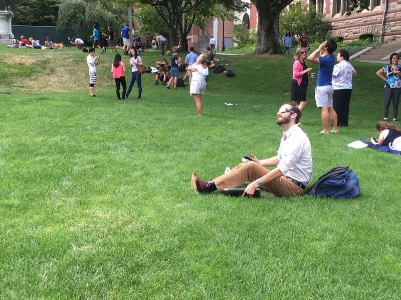 Relaxing and watching the eclipse from a lawn on the Brown University campus.