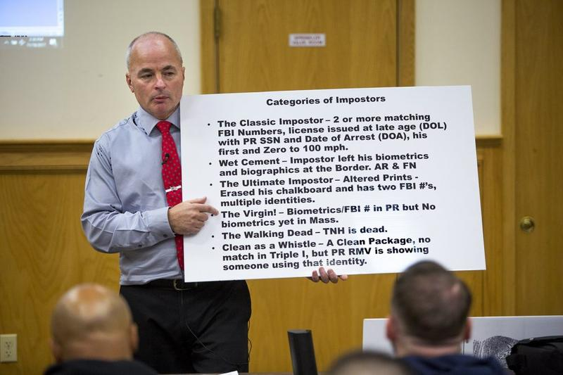 "Officer James Scott of the Saugus Police Department holds up a placard with the categories of so-called ""impostors"" during an impostor training class at Bristol County Jail and House of Correction in North Dartmouth."