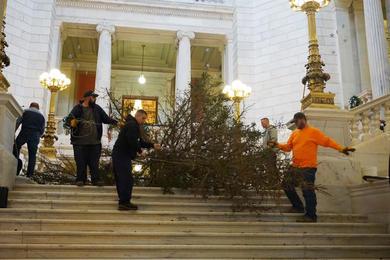 Workers take the 25-foot statehouse Christmas tree down, after it lost most of its needles. It will be replaced.