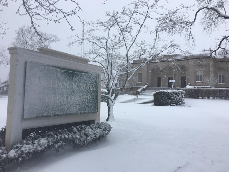 A snow covered sign in front of a Cranston library.