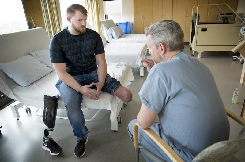 Brandon Korona, an Army veteran whose left leg was injured in an IED explosion in Afghanistan, talks with Dr. Matthew Carty at Brigham and Women's Faulkner Hospital in Boston.