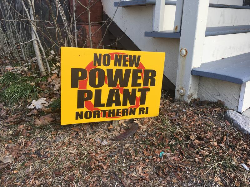 An anti-power plant sign is displayed in the front yard of a property in Providence.