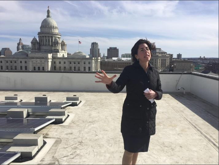Rhode Island Governor Gina Raimondo speaks about the state's energy use reduction goals as she stands next to new solar panels on the roof of the state Department of Administration building.