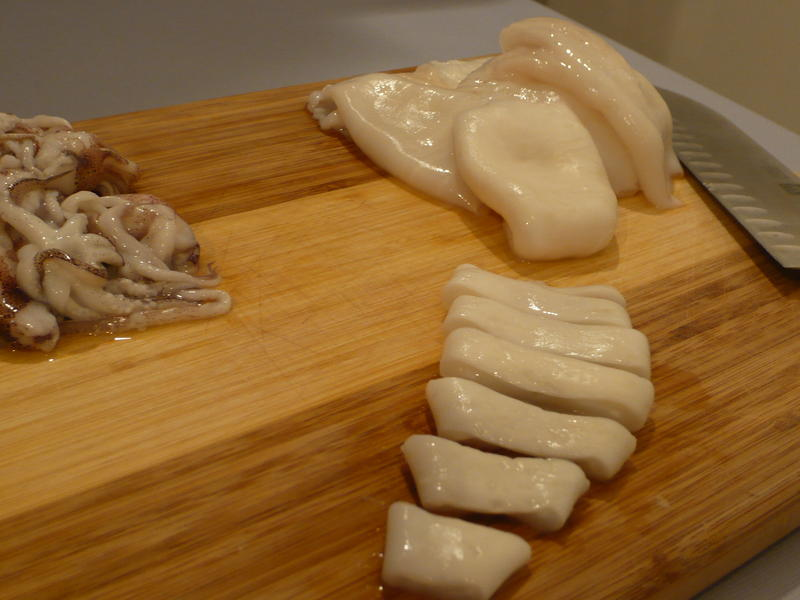 A squid is sliced in preparation for a calamari dish.