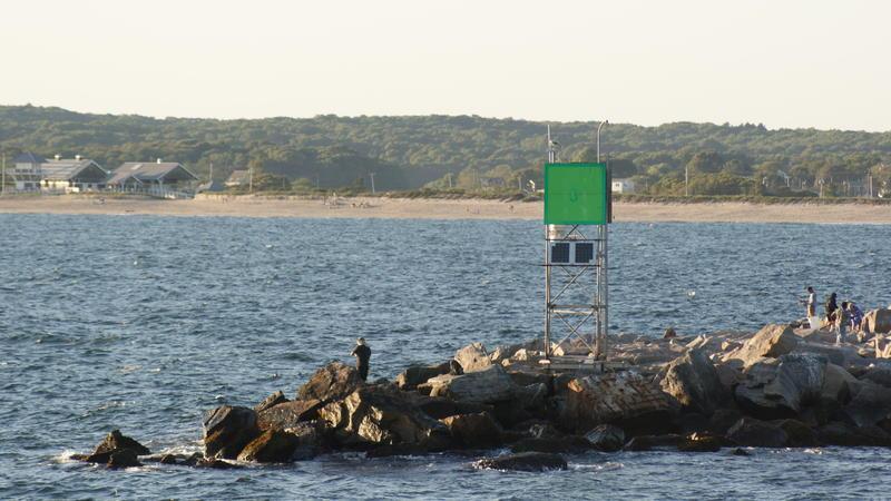 A fisherman stands on the rocks in Galilee in Rhode Island