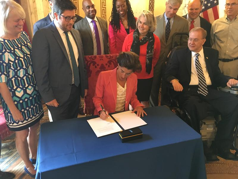 Governor Gina Raimondo signs an executive order last September appointing Shaun O'Rourke (left to the governor) as the state's first-ever cheif resiliency officer. O'Rourke was tasked with developing a statewide plan for preparing for climate change.