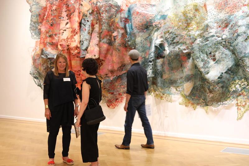 """Artist Joan Hall in front of her work in the exhibit """"Sea of Heartbreak."""""""