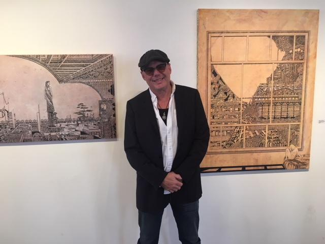 Artist-musician Lennie Peterson stands with two of his pieces.