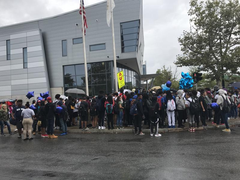 People surround the vigil set on the sign of Providence Technical and Career Academy Sign