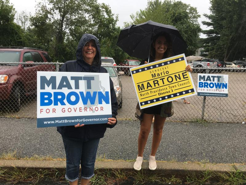 Campaign volunteers stood in front of a polling place with signs, undetered by the wet weather