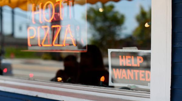 A Help Wanted sign is seen in the window of Fellini Pizzeria in Providence. Rhode Island?s unemployment rate declined fractionally in April for the second straight month. Photo by Alex Nunes.