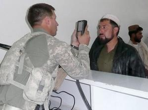 A U.S. soldier at a border immigration center takes an eye scan of an Afghan man. That information is entered into a database and cross-checked with an insurgent watch list. Rachel Martin/NPR.