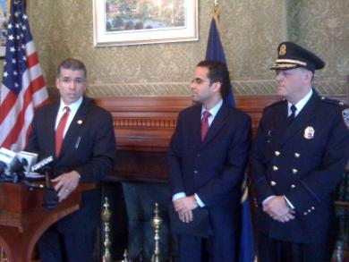 Police Commissioner Steven Pare outlines the report as Mayor Angel Taveras and Col. Dean Esserman look on.