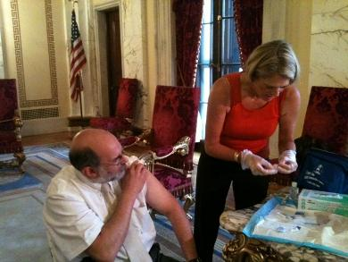 Stephanie Chafee prepares to give Dr. Michael Fine his flu shot