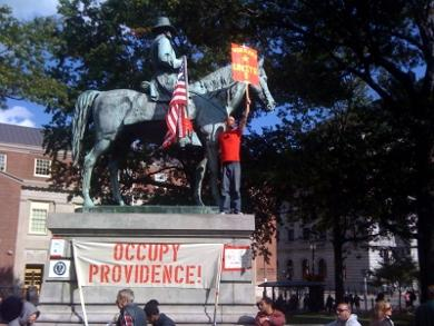 Tom Sullivan holds a sign while perched on the statue of Gen. Ambrose Burnside.