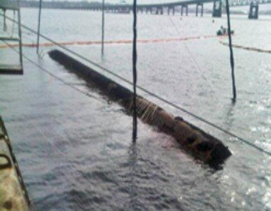 Sunken barge surfaces during the salvage effort