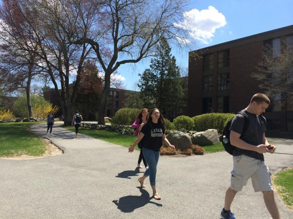 Students walk through Bryant University's campus in the warm weather.  Bryant University students average the highest student debt in Rhode Island.