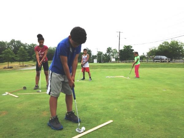 Kids learning the perfect putt at Button Hole Golf course in Providence.