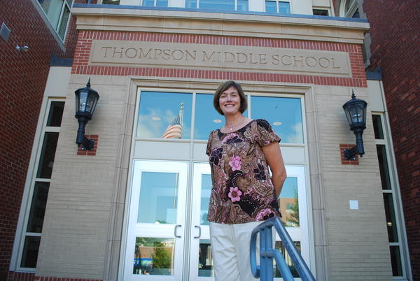 Science teacher Barbara Walton Faria stands in front of Thompson Middle School in Newport