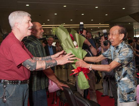 Flute player Lu Chunling, who performed at the Arrival Ceremony at the Shanghai Pudong Airport, presents flowers to Orchestra violinist Davyd Booth, one of the original Orchestra members to have been part of the 1973 Tour of China.