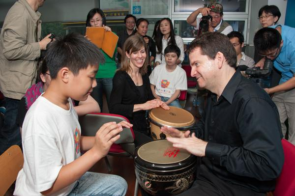 Philadelphia Orchestra members with autistic children during an in-school program at a Youth Center in Shanghai. Percussionists Christopher Deviney (front) and Angela Zator Nelson work with one student as he tries his hand at the drums.