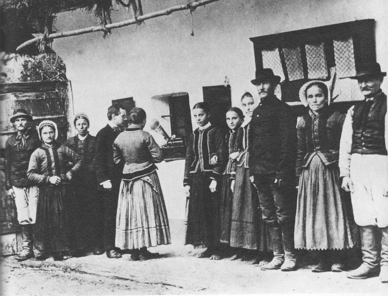 Hungarian composer and pianist Béla Bartók listens to folk music on a phonograph with villagers, 1907.