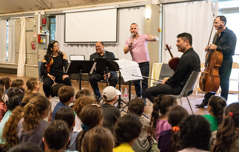 Yannick addresses a group of children at an outreach concert at Neve Shalom with Orchestra quartet: (left to right) Amy Oshiro-Morales, violin; Ricardo Morales, principal clarinet; Ohad (Udi) Bar-David, cello; Meng Wang, viola.