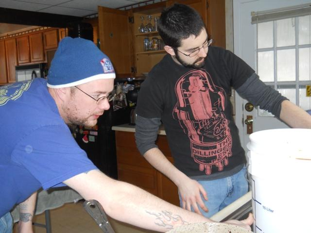 Homebrewers Owen McLaughlan and Jon Peck check the water level of a soon-to-be stout.