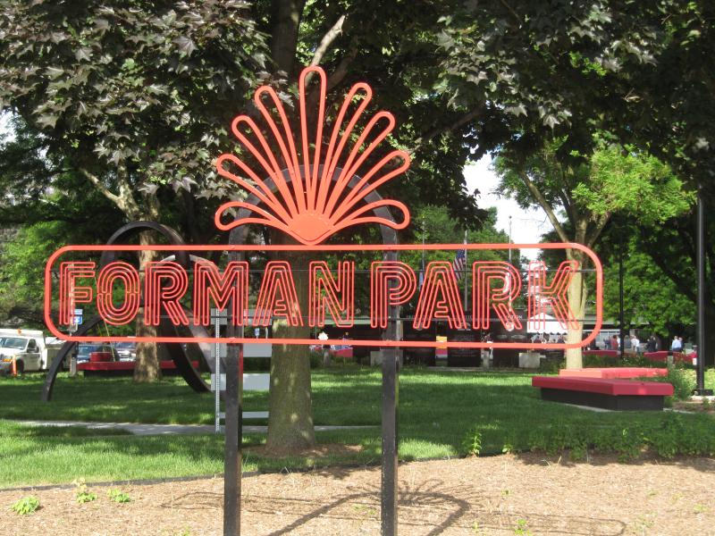 A vibrant sign shows off new renovations to Forman Park. The park splits the east and westbound lanes of East Genesee Street in Syracuse.
