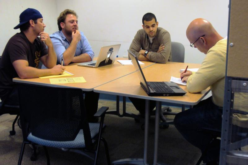 Entrepreneur-in-Residence John Liddy, right, meets with one of the teams participating in the Syracuse Student Sandbox.