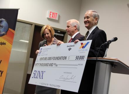 Venture Jobs Foundation President Denny DeLeo (right) accepts a $50,000 check from 5LINX CEO Craig Jerabeck. Monroe County Executive Maggie Brooks is at left.