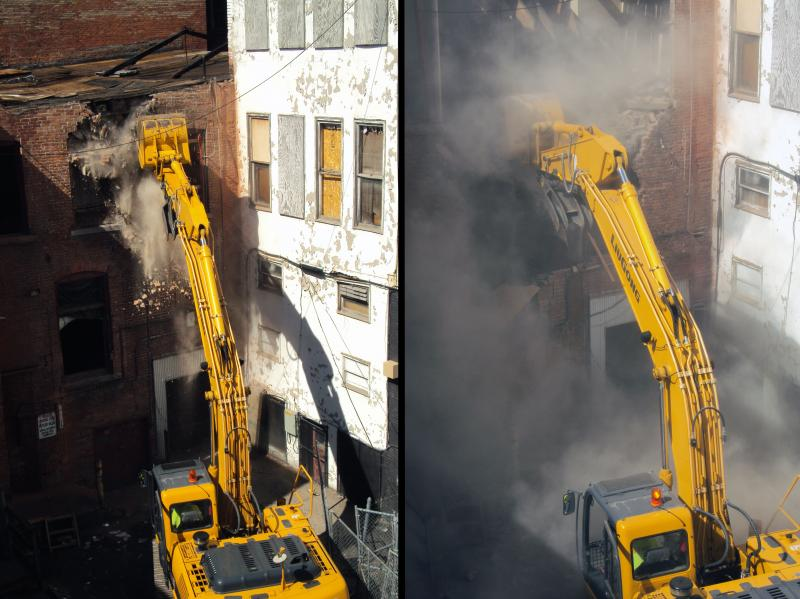 A backhoe demolishes the back of the Bond Building in downtown Syracuse for part of the Pike Block project.