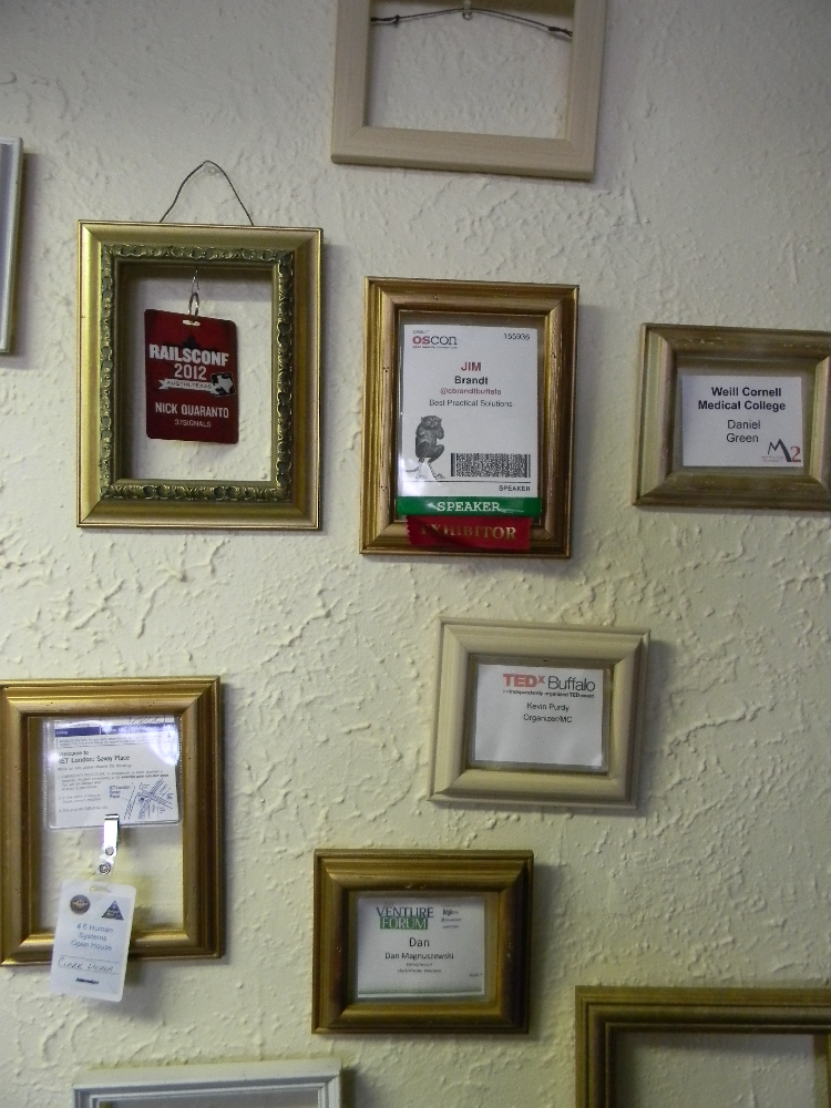 Wall decorations are ad hoc. Here, name badges from conferences are loosely framed.