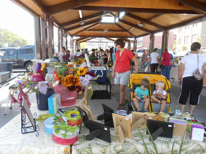 Shoppers and vendors shelter from the sun under a new pavilion at the Saturday Farmers Market in Watertown.