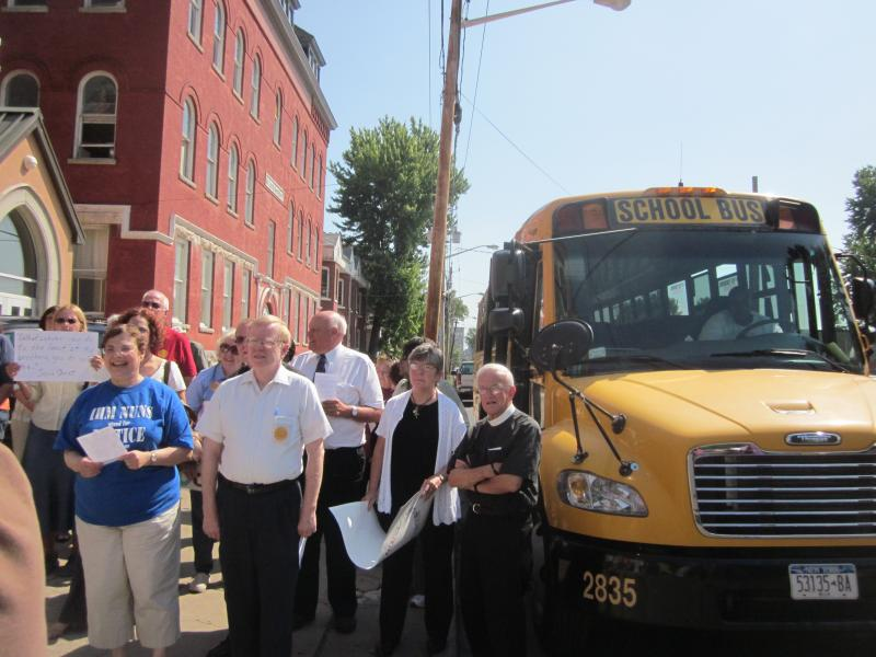 Members from various faith communities travel through Syracuse by school bus in solidarity with the Nuns on the Bus movement.