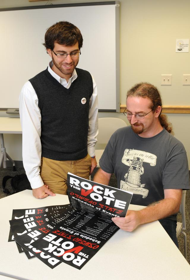 Graduate history major Jon Zella of the Civic Engagement Coalition and graduate human-computer interaction major Phillip Moore look over promotion for the Rock the Vote campaign.