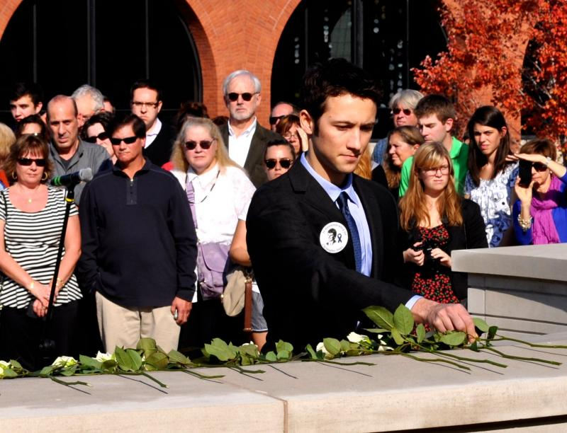 An SU Remembrance Scholar lays down a rose in memory of a victim of the Pan-Am Flight 103 bombing.
