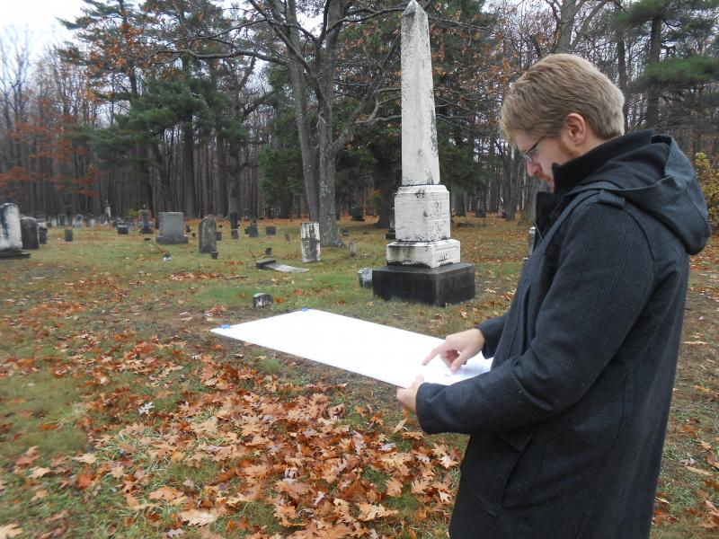 Michael Sprowles, of Fort Drum's cultural resources office, checks a new map to locate grave sites at Sheepfold Cemetery on Fort Drum.