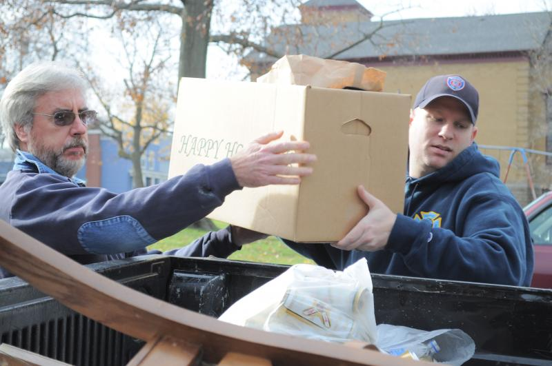 Volunteers from the Oswego Fire Department help to load supplies for a Thanksgiving dinner into a family's truck.